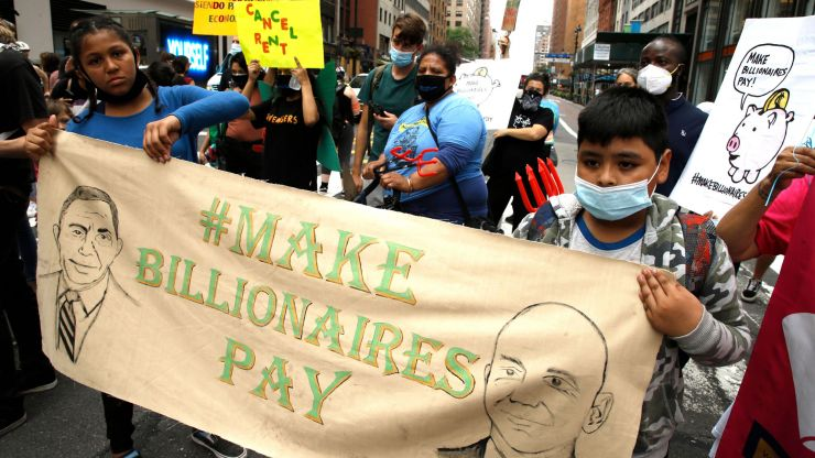 "Children protesting and holding a sign that says ""Make Billionaires Pay."""