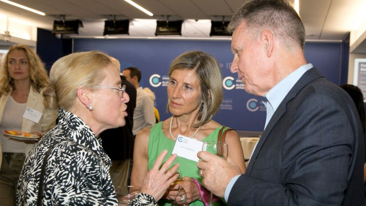 Three people talk during a Council event reception