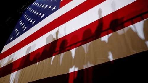 Image of an American flag with a crowd behind it.