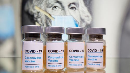"Vials with a sticker reading, ""COVID-19 / Coronavirus vaccine / Injection only"" are seen in front of a displayed U.S. dollar banknote with George Washington and a printed mask"
