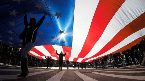 People carry the American Flag during a Veteran's Day parade