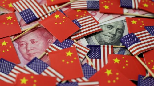 A US dollar banknote featuring American founding father Benjamin Franklin and a China's yuan banknote featuring late Chinese chairman Mao Zedong are seen among US and Chinese flags.