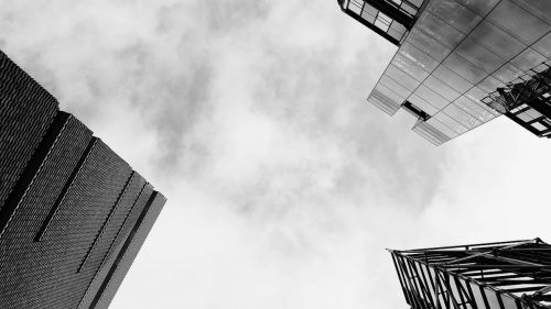 A black and white photo of the view from the ground below three skyscrapers